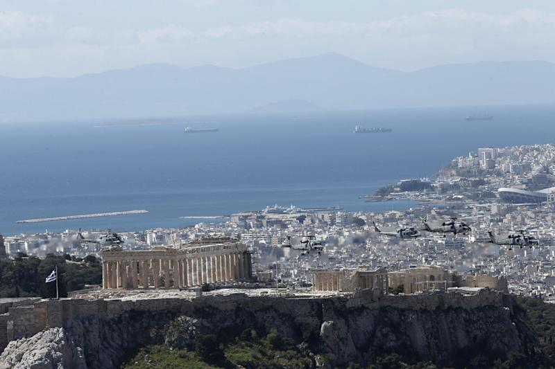 Military helicopters fly over the ancient Acropolis hill during a parade in Athens, Tuesday, March 25, 2014, to commemorate Greek Independence Day. The national holiday on March 25 marks the start of Greece's 1821 war of independence against the 400-year Ottoman rule. (AP Photo/ Petros Giannakouris)