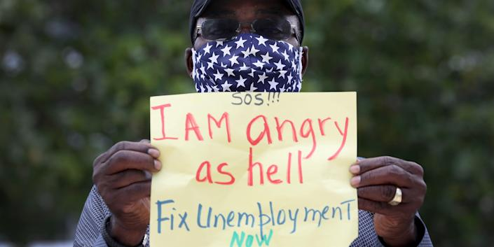 an unemployed worker holds a sign that says  I Am angry as hell Fix Unemployment Now,'
