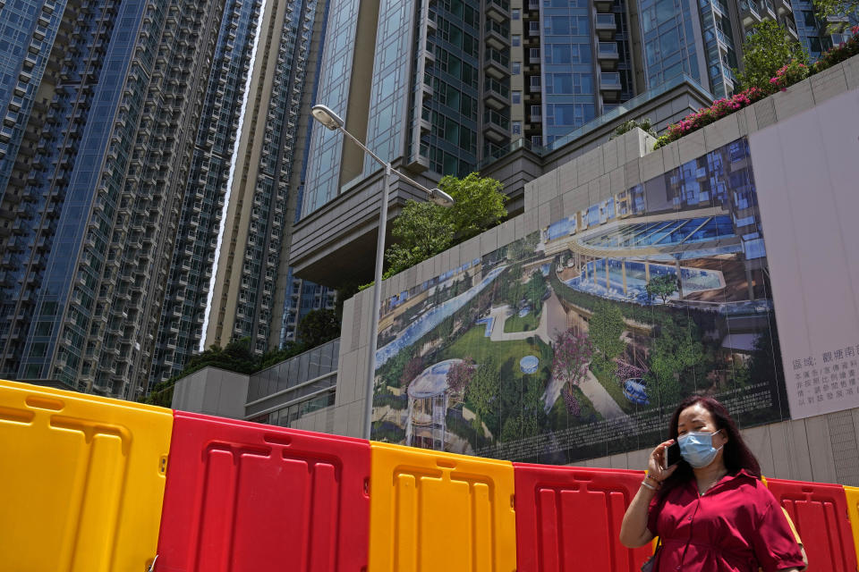 In this Tuesday, June 15, 2021, photo, a woman walks in front of the Grand Central residential building complex where one of the HK$10.8 million (US$1.4 million) 449 square feet single-room flats will be offered as a prize in a lucky draw. Coronavirus vaccine incentives offered by Hong Kong companies, including a lucky draw for an apartment, a Tesla car and even gold bars, are helping boost the city's sluggish inoculation rate. (AP Photo/Kin Cheung)