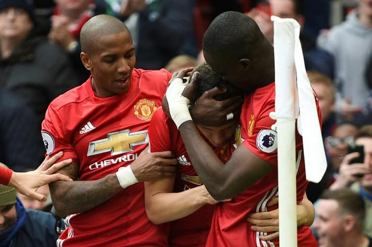 Manchester United's Ashley Young (L) and Eric Bailly (R) congratulate Ander Herrera after he scored their second goal against Chelsea
