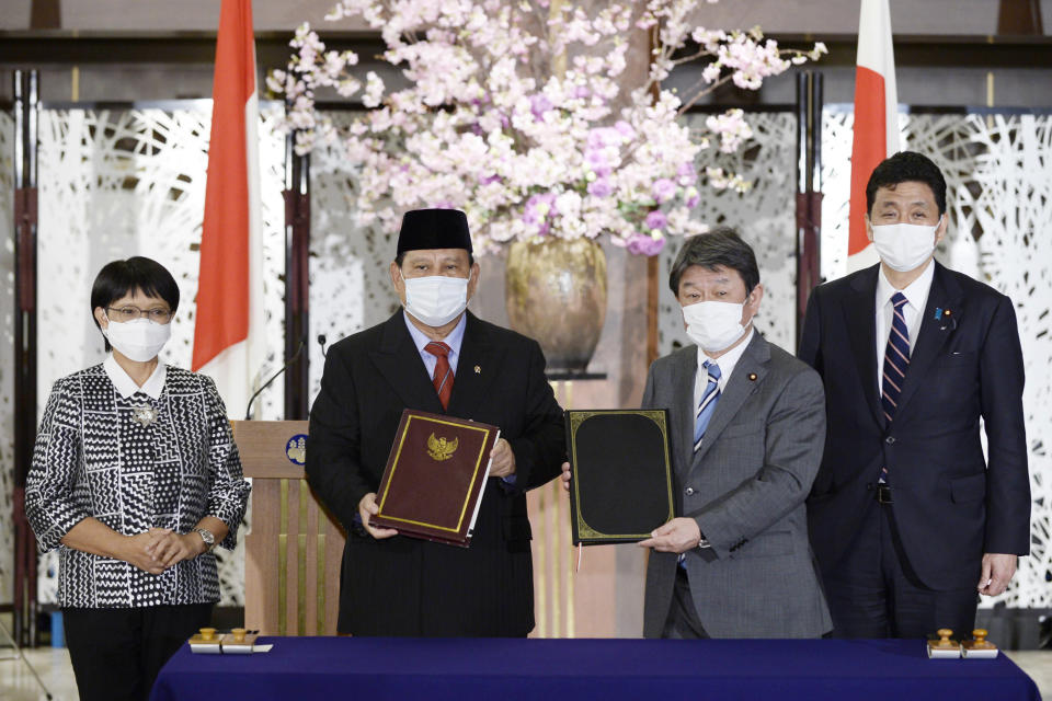 Indonesian Foreign Minister Retno Marsudi, from left, Defense Minister Prabowo Subianto, Japanese Foreign Minister Toshimitsu Motegi and Defense Minister Kishi Nobuo pose for a photo during a signing ceremony for their foreign and defense ministers' meetings in Tokyo on Tuesday, March 30, 2021. (David Mareuil/Pool Photo via AP)