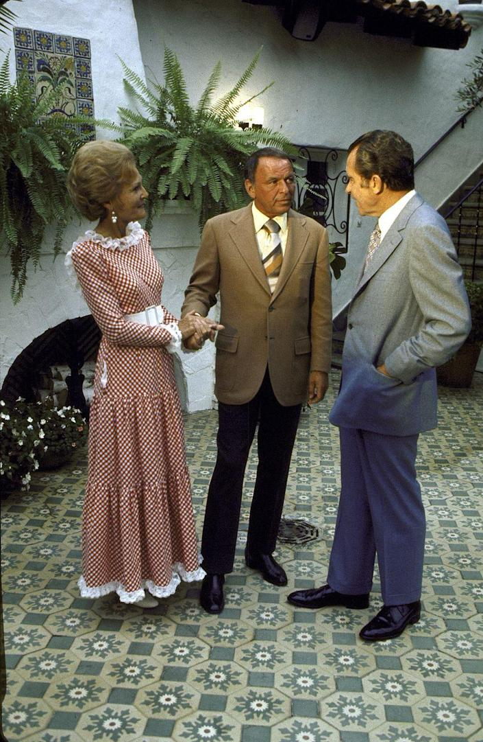 <p>The President and First Lady welcome Frank Sinatra into their home in San Clemente, California for a fundraising event in 1972.</p>