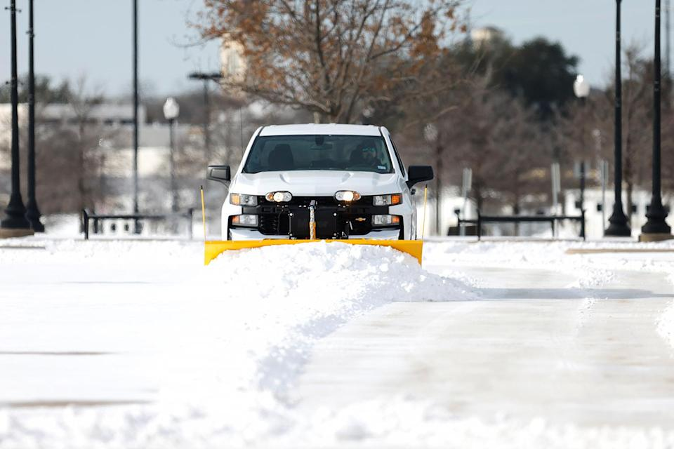 <p>A truck plows the parking lot at Dickies Arena on Feb. 16 in Fort Worth, Texas.</p>