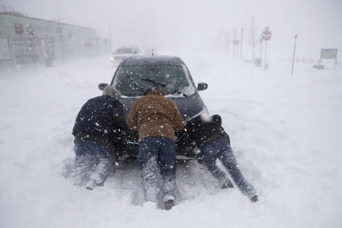 <p>A group of men help a motorist after his vehicle was stuck in the snow near Asbury Park boardwalk during a snowstorm, Thursday, Jan. 4, 2018, in Asbury Park, N.J. (Photo: Julio Cortez/AP) </p>