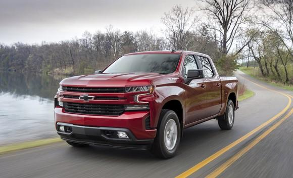 A red 2019 Chevrolet Silverado, a full-size pickup, on a country road.