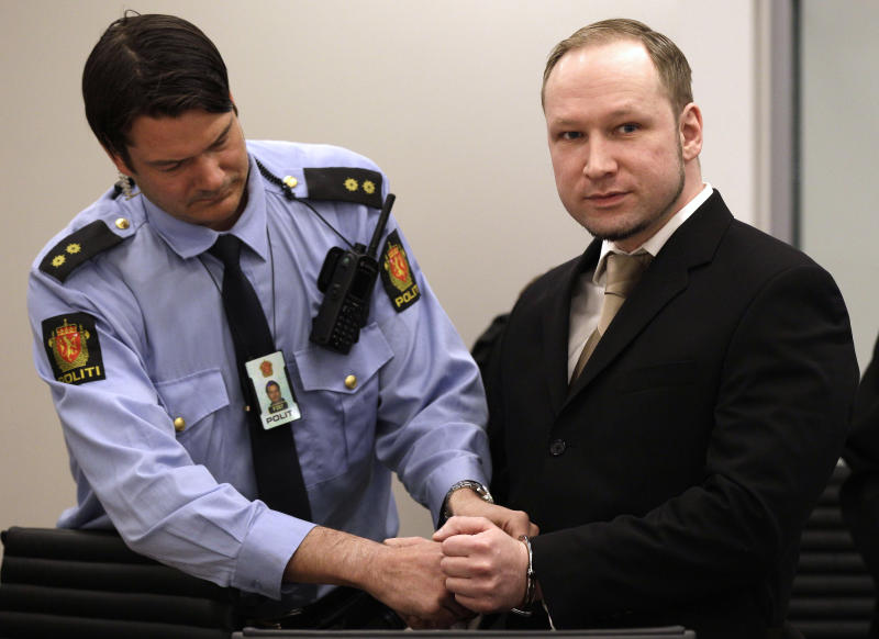A court officer unlocks the handcuffs of Norwegian Anders Behring Breivik, right, as he appears in court to face terrorism and premeditated murder charges, Oslo, Norway, Monday, April 16, 2012. Breivik, who confessed to killing 77 people in a bomb-and-shooting massacre went on trial in Norway's capital Monday, defiantly rejecting the authority of the court. (AP Photo/Frank Augstein)