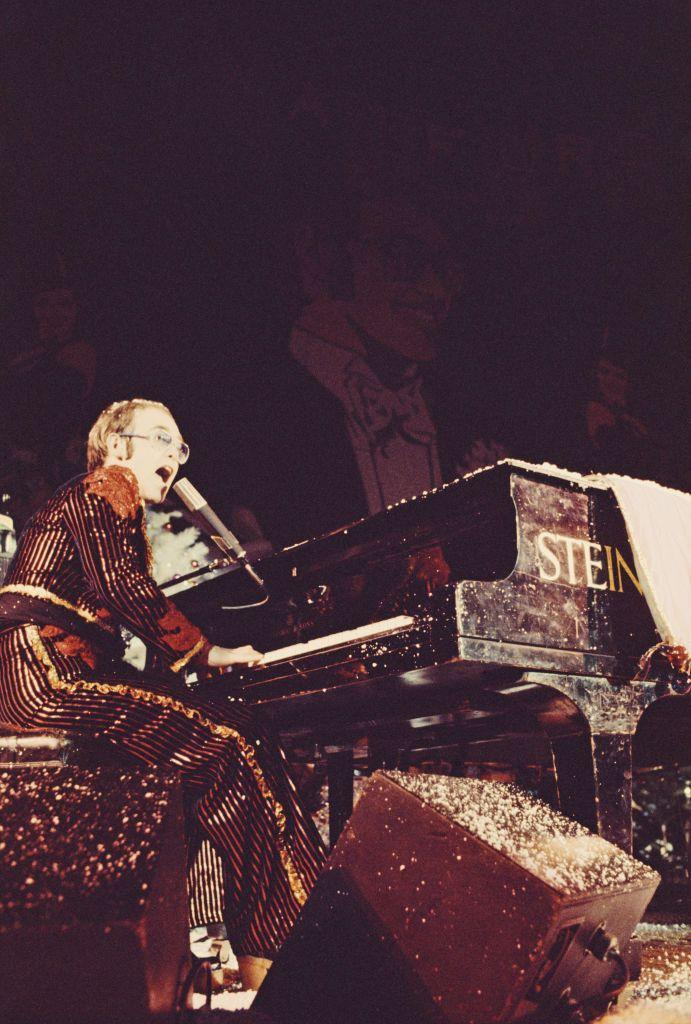 <p>Elton John didn't fall short on festive attire when he performed at the Hammerstein Ballroom in London in 1974. The musician wore a head-to-toe red glitter and sequin suit on a snow-covered stage. </p>