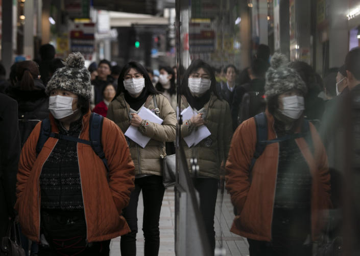 Commuters wearing protective face masks walk on a sidewalk Monday, Jan. 27, 2020, in the Shinjuku district of Tokyo. China has extended its Lunar New Year holiday three more days to discourage people from traveling as it tries to contain the spread of a viral illness that has caused dozens of deaths. (AP Photo/Jae C. Hong)