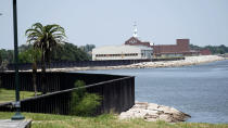 """A seawall, which will be increased in size, is shown along the banks near downtown Thursday, July 26, 2018, in Port Arthur, Texas. The oil industry wants the government to help protect some of its facilities on the Texas Gulf Coast against the effects of global warming. One proposal involves building a nearly 60-mile """"spine"""" of flood barriers to shield refineries and chemical plants. Many Republicans argue that such projects should be a national priority. But others question whether taxpayers should have to protect refineries in a state where top politicians still dispute whether climate change is real. (AP Photo/David J. Phillip)"""