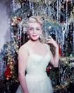 <p>Film star Lana Turner dazzles in a white gown while standing in front of an equally glitzy Christmas tree. </p>