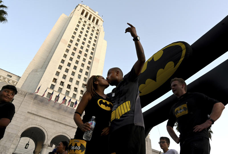 Maria Garcia kisses her husband Jose Garcia of Los Angeles after completing the Batman Inaugural 5K run on Batman's 80th anniversary at Grand Park on Saturday, Sept. 21, 2019, in Los Angeles. (Keith Birmingham/The Orange County Register via AP)
