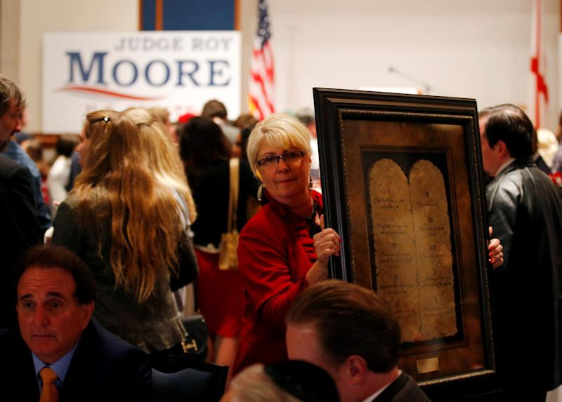 A framed Ten Commandments is being carried by a supporter at Republican Roy Moore's election party in Montgomery, Alabama, U.S., December 12, 2017.