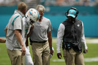 Miami Dolphins quarterback Tua Tagovailoa (1) is helped off the field after being injured, as Miami Dolphins head coach Brian Flores, right, looks on, during the first half of an NFL football game, Sunday, Sept. 19, 2021, in Miami Gardens, Fla. (AP Photo/Wilfredo Lee)