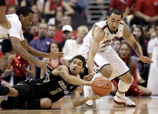 Colorado's Askia Booker, center, looks to pass after retrieving a loose ball against Arizona's Jordin Mayes, left, and Brendon Lavender during the first half of an NCAA college basketball game in the finals of the Pac-12 conference championship in Los Angeles, Saturday, March 10, 2012. (AP Photo/Jae C. Hong)