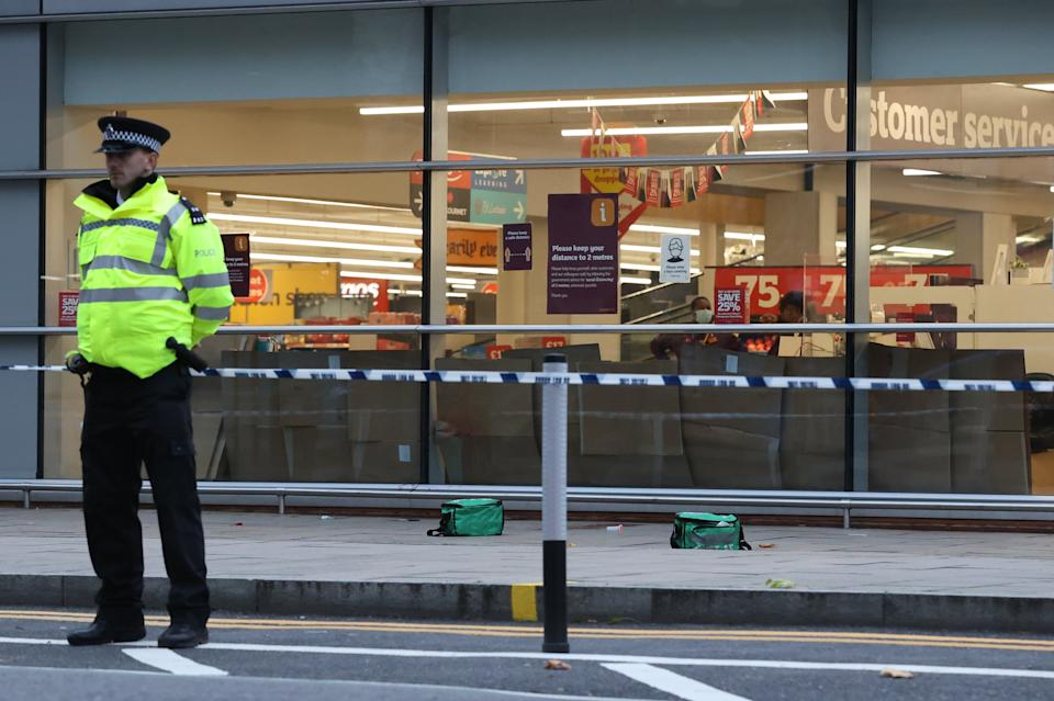 A police officer stands guard outside the supermarket on FridayNigel Howard