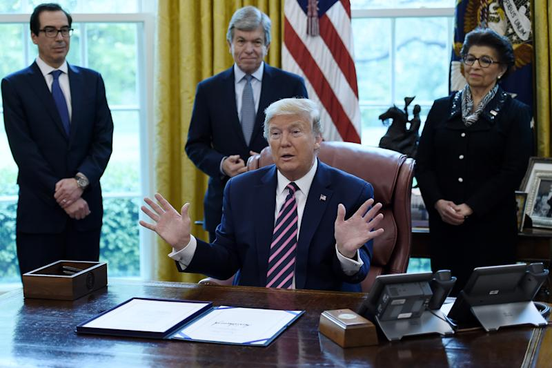 US President Donald Trump gestures as he speaks after signing the Paycheck Protection Program and Health Care Enhancement Act in the Oval Office of the White House in Washington, DC, on April 24, 2020. - The $483 billion stimulus act will back small businesses on the brink of bankruptcy, and allocate more money for health-care providers and virus testing. (Photo by Olivier DOULIERY / AFP) (Photo by OLIVIER DOULIERY/AFP via Getty Images)