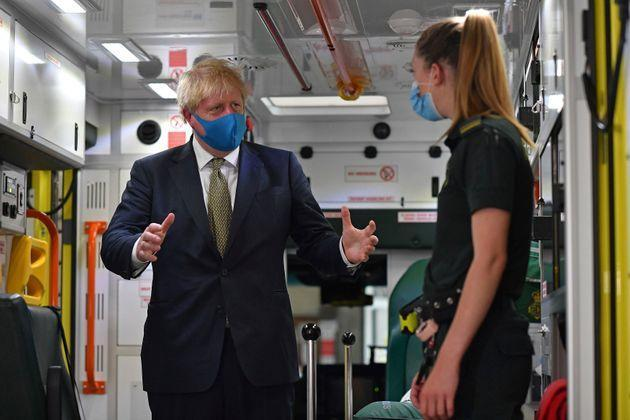 Prime minister Boris Johnson, wearing a face mask, talks with a paramedic as they stand inside the back of an ambulance during a visit to the headquarters of the London Ambulance Service NHS Trust in London.