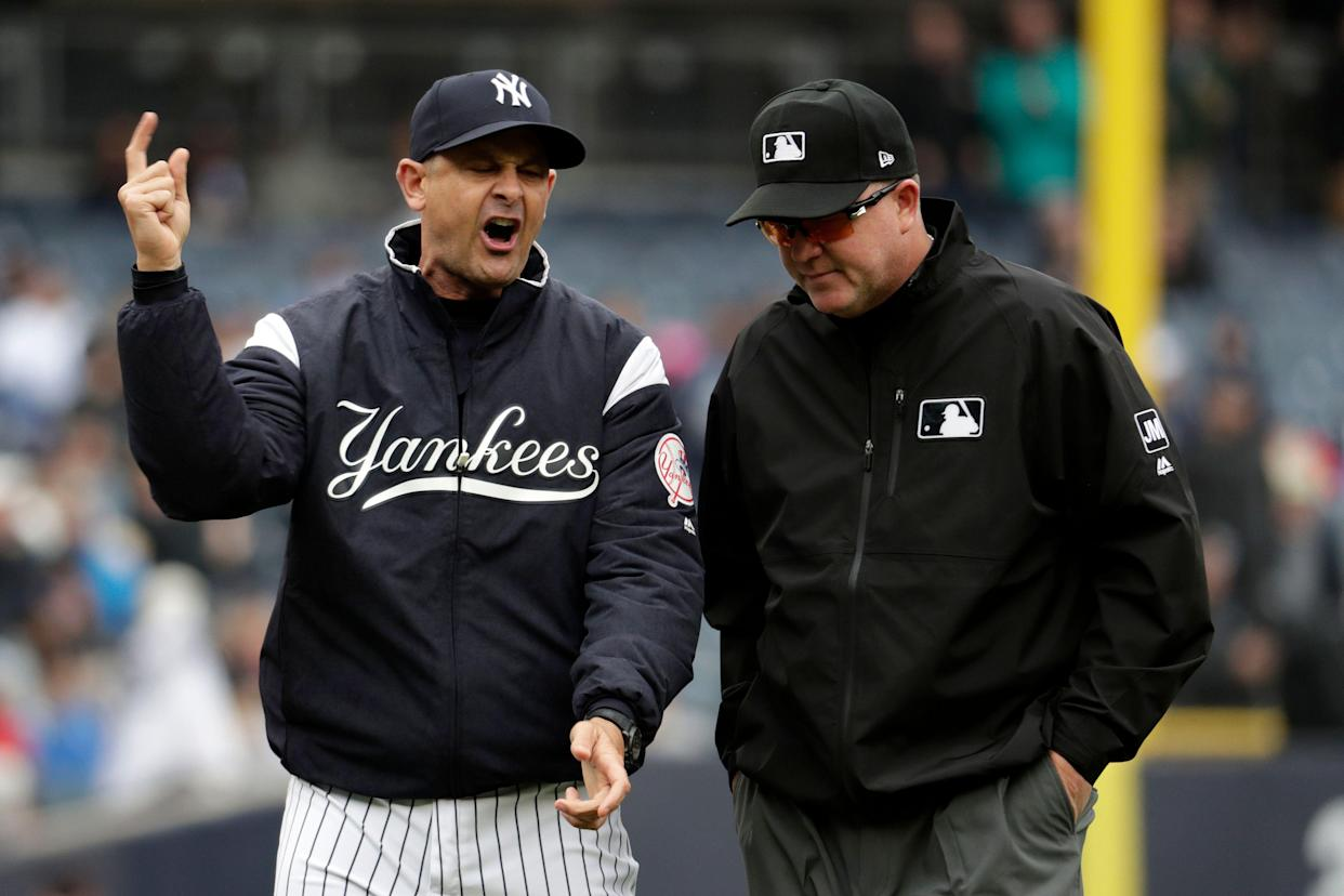 Yankees manager Aaron Boone reacts after fan interference took away a three-run home run for Gleyber Torres. (AP Photo/Julio Cortez)