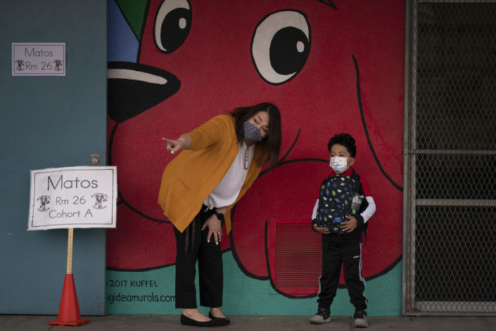 """FILE - In this April 13, 2021, file photo, kindergarten teacher Lilia Matos and her student Jesus Mendez stand outside their classroom on the first day of in-person learning at Heliotrope Avenue Elementary School in Maywood, Calif. California's public schools have seen a """"sharp decline"""" in enrollment this year as the pandemic forced millions into online school and districts dawdled in bringing children back to the classroom. Data from the California Department of Education released Thursday, April 22, 2021, shows the number of students at K-12 schools dropped by more than 160,000 this academic year, most of them in K-6. (AP Photo/Jae C. Hong, File)"""