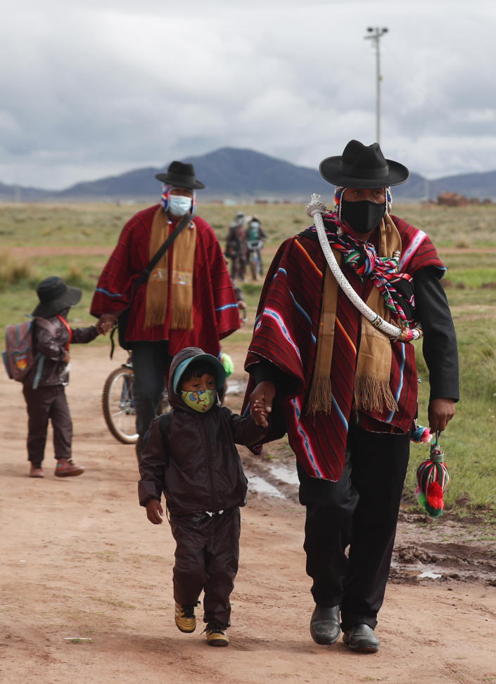 Aymara Indigenous fathers walk their children wearing new, protective uniforms amid the COVID-19 pandemic to Jancohaqui Tana school during their first week back to class amid the pandemic near Jesus de Machaca, Bolivia, early Thursday, Feb. 4, 2021. (AP Photo/Juan Karita)