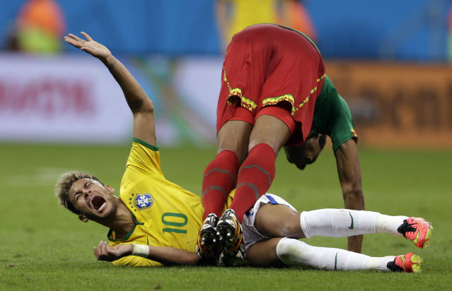 Brazil's Neymar cries in pain after colliding with Cameroon's Joel Matip during the group A World Cup soccer match between Cameroon and Brazil at the Estadio Nacional in Brasilia, Brazil, Monday, June 23, 2014. (AP Photo/Andre Penner)