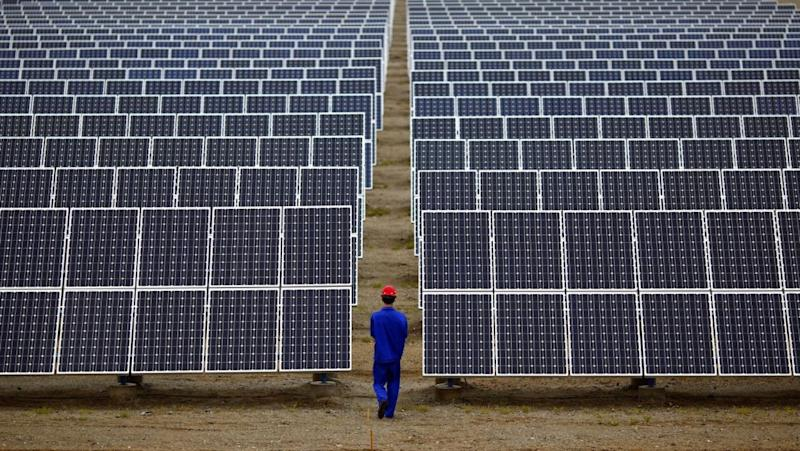A worker inspects solar panels at a solar Dunhuang, 950km (590 miles) northwest of Lanzhou, Gansu Province September 16, 2013.