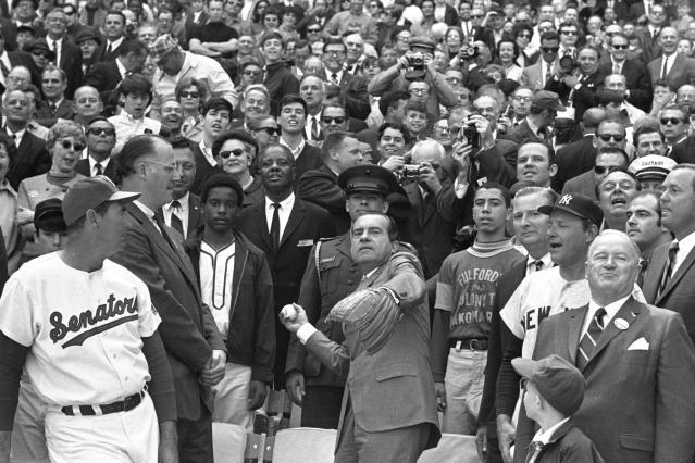 FILE - In this April 7, 1969, file photo, President Richard M. Nixon throws out the ceremonial first pitch in Washington as Baseball Commissioner Bowie Kuhn, second from left, and Washington Senators manager Ted Williams, far left, and others, look on. Growing up in the Washington suburbs during the 1960s, the local baseball team was a lost cause, except for a winning record for the expansion Senators after Ted Williams was lured out of retirement to manage the team. (AP Photo, File)
