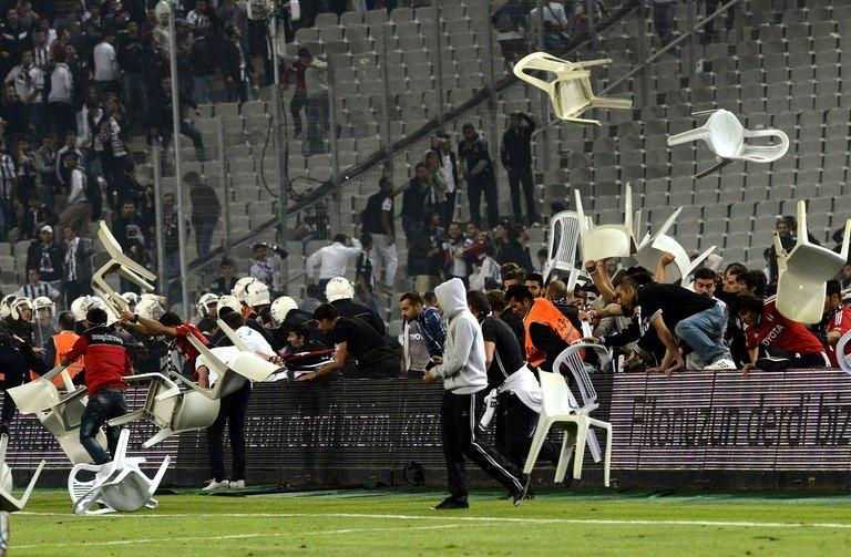 Besiktas football team supporters fight with anti-riot police officers on September 22, 2013, at the Ataturk stadium