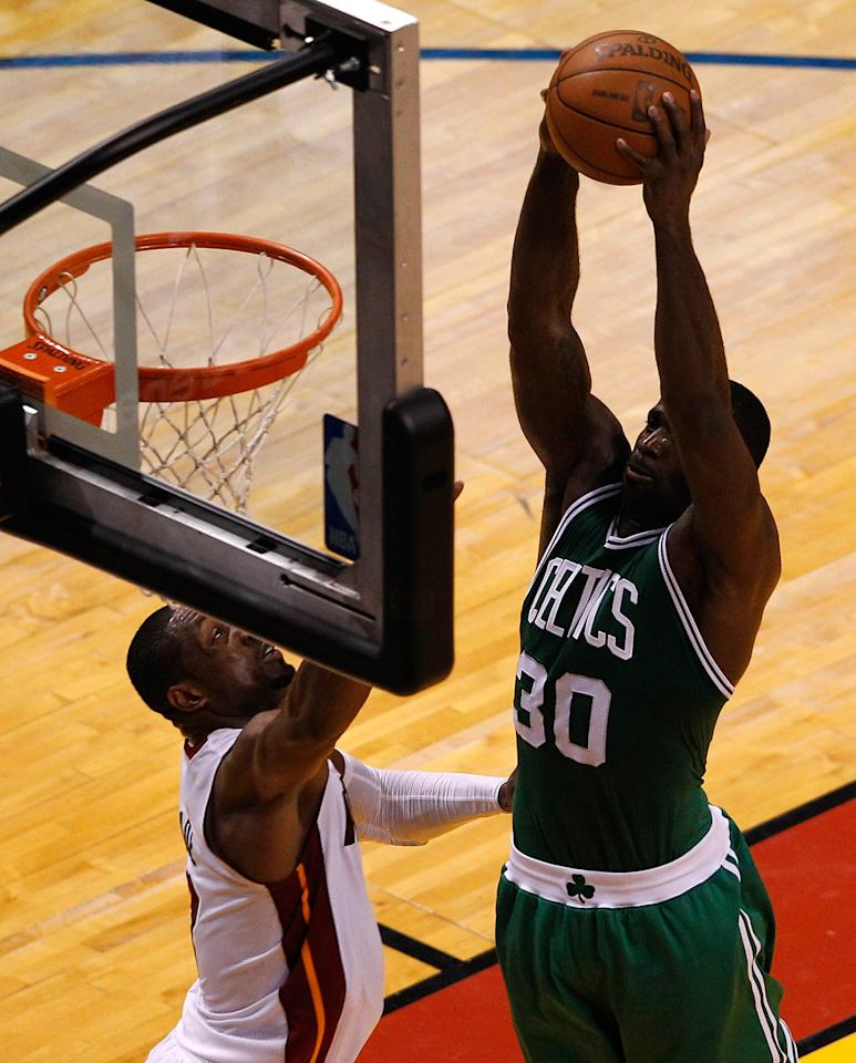 MIAMI, FL - JUNE 09:  Brandon Bass #30 of the Boston Celtics goes up for a dunk over Dwyane Wade #3 of the Miami Heat in the first half in Game Seven of the Eastern Conference Finals in the 2012 NBA Playoffs on June 9, 2012 at American Airlines Arena in Miami, Florida. NOTE TO USER: User expressly acknowledges and agrees that, by downloading and or using this photograph, User is consenting to the terms and conditions of the Getty Images License Agreement.  (Photo by J. Meric/Getty Images)