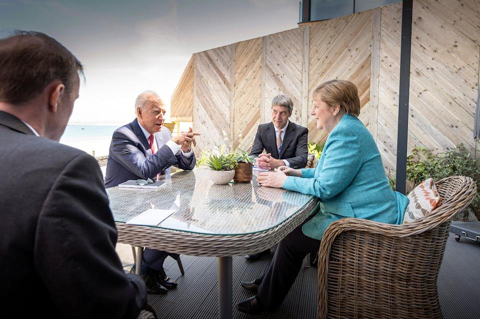 President Joe Biden and German Chancellor Angela Merkel meet on the sidelines of the G7 summit in St. Ives, England. With them are their foreign policy advisors Jan Hecker and Jake Sullivan.