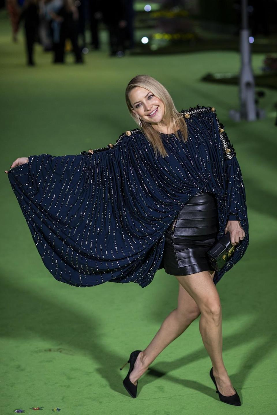 A woman in a blue shirt and black miniskirt posing on a green carpet