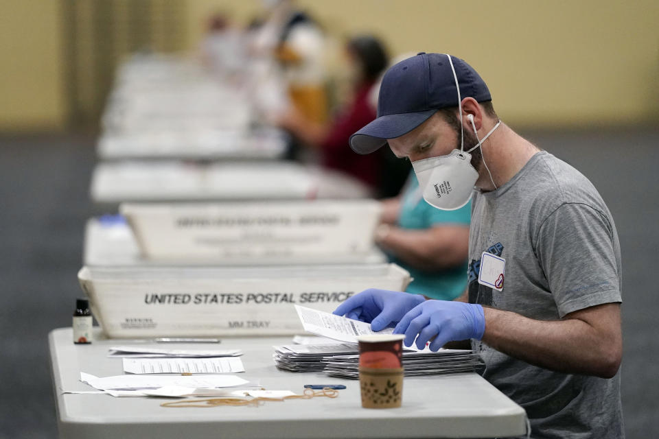 Workers prepare mail-in ballots for counting, Wednesday, Nov. 4, 2020, at the convention center in Lancaster, Pa., following Tuesday's election. (AP Photo/Julio Cortez)