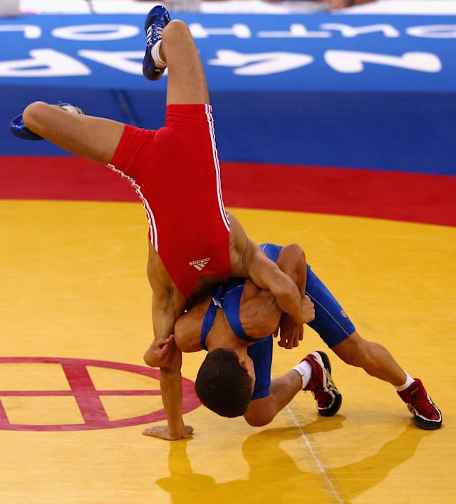 SINGAPORE - AUGUST 15: Elman Mukhtarov of Azerbaijan competes against Nurbek Hakkulov of Uzbekistan in the final of the Men's Greco Roman 50kg Wrestling competition on day one of the Youth Olympics at the International Convention Centre on August 15, 2010 in Singapore. (Photo by Mark Dadswell/Getty Images)