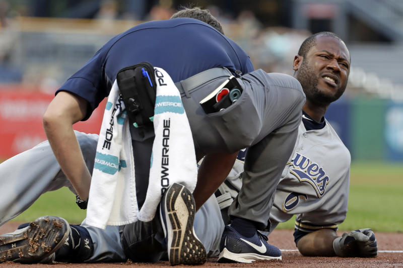 Milwaukee Brewers' Lorenzo Cain, right, is grimaces as he is checked by a team trainer after fouling a ball off his leg while batting during the first inning of the team's baseball game against the Pittsburgh Pirates in Pittsburgh, Tuesday, Aug. 6, 2019. Cain finished the at-bat and left the game. (AP Photo/Gene J. Puskar)