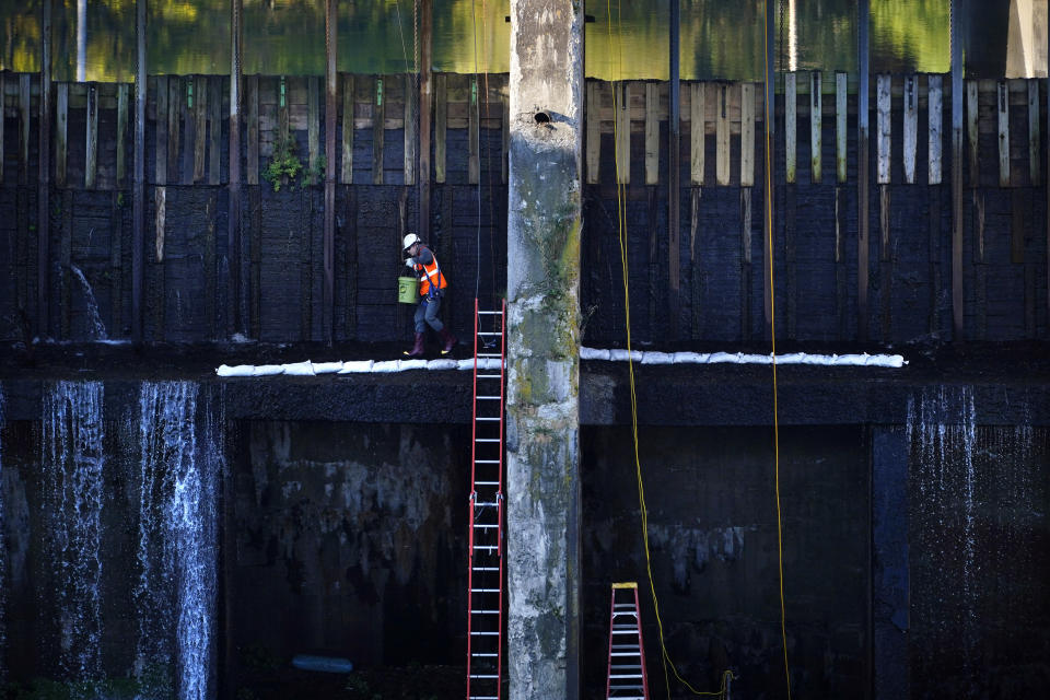 A worker places a line of sand bags on the downstream wall of a dam at Weston Station on the Kennebec River, Tuesday, Sept. 14, 2021, in Skowhegan, Maine. The dam has provided hydro-electric power for over 100 years. (AP Photo/Robert F. Bukaty)