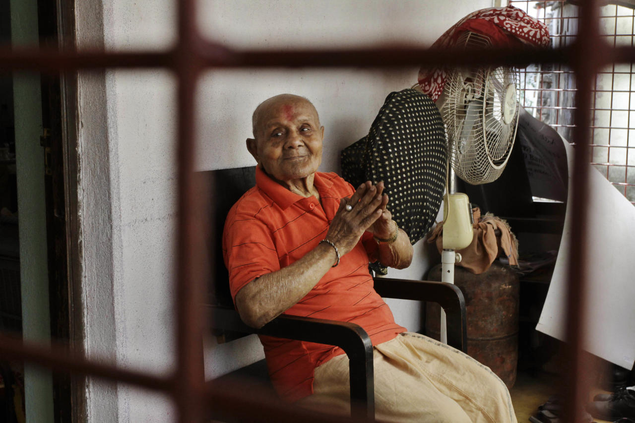 Indian body builder Manohar Aich sits in the balcony in Kolkata, India, Sunday, March 18, 2012. Aich, a former Mr. Universe who has just turned 100 said Sunday, that happiness and a life without tensions are the key to his longevity. Aich, who is 4 foot 11 inches (150 centimeters) tall, overcame many hurdles, including grinding poverty and a stint in prison, to achieve body building glory. (AP Photo/Bikas Das)