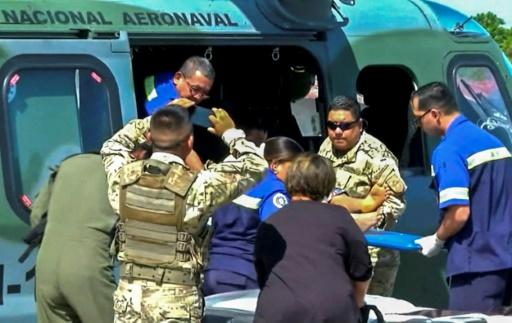 Paramedics carrying one of 15 people rescued from a religious sect in Panama's Veraguas province, close to an area where a mass grave containing seven bodies was found