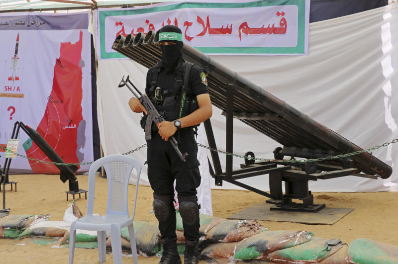FILE - In this July 20, 2016 file photo, a masked Palestinian militant from the Izzedine al-Qassam Brigades, a military wing of Hamas, stands in front of rocket launchers during a weapon exhibition at a Hamas-run youth summer camp, in Gaza City. Over the years, the Islamic militant Hamas group has built up a large arsenal of rockets and missiles that have evolved from rudimentary short-range projectiles into powerful weapons capable of striking virtually anywhere in Israel. (AP Photo/Adel Hana, File)