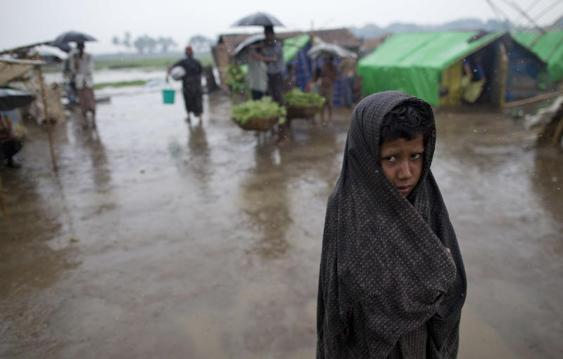 An internally displaced Rohingya boy wraps himself with a sarong as he walks in rain at a makeshift camp for Rohingya people in Sittwe, northwestern Rakhine State, Myanmar, ahead of the arrival of Cyclone Mahasen, Tuesday, May 14, 2013. The U.N. said the cyclone, expected later this week, could swamp makeshift housing camps sheltering tens of thousands of Rohingya. Myanmar state television reported Monday that 5,158 people were relocated from low-lying camps in Rakhine state to safer shelters. But far more people are considered vulnerable. (AP Photo/Gemunu Amarasinghe)
