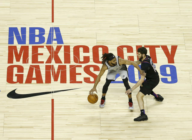 San Antonio Spurs' Patty Mills dribbles that ball as Phoenix Suns' Tyler Johnson defends in the first half of their regular-season NBA basketball game in Mexico City, Saturday, Dec. 14, 2019. (AP Photo/Rebecca Blackwell)