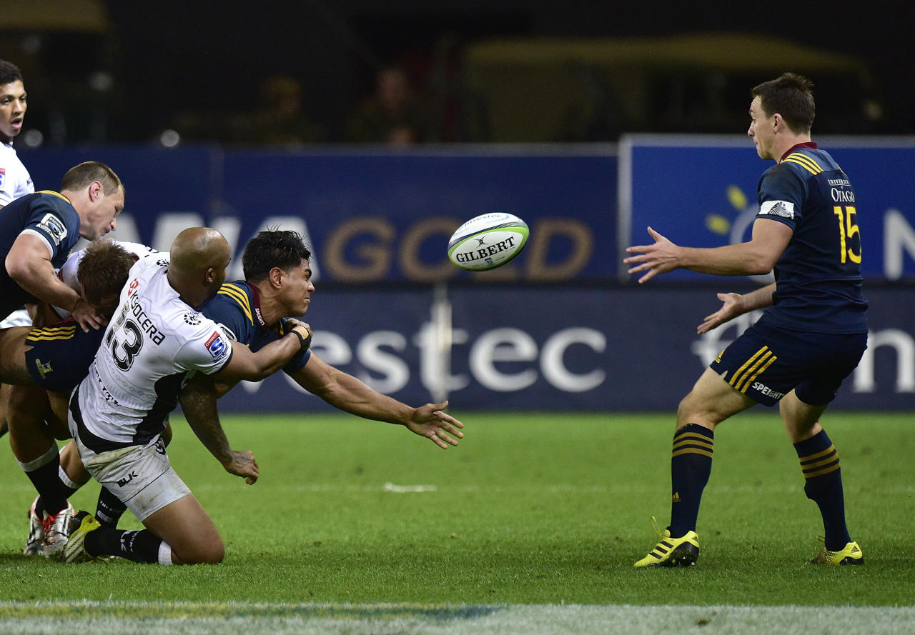 Highlanders' Malakai Fekitoa (C) passes the ball to teammate Ben Smith (R) as he is tackled by Sharks' JP Pietersen (L) during the Super Rugby match between New Zealand's Otago Highlanders and South Africa's Coastal Sharks at Forsyth Barr Stadium in Dunedin on April 22, 2016. (AFP Photo/Marty Melville)