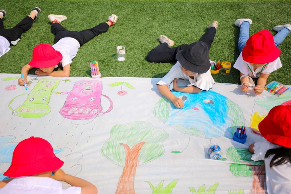 Children draw paintings of environmental protection on a canvas at a kindergarten ahead of World Environment Day on June 2, 2020 in Nantong, Jiangsu Province of China. (Photo by Xu Hui/VCG via Getty Images)