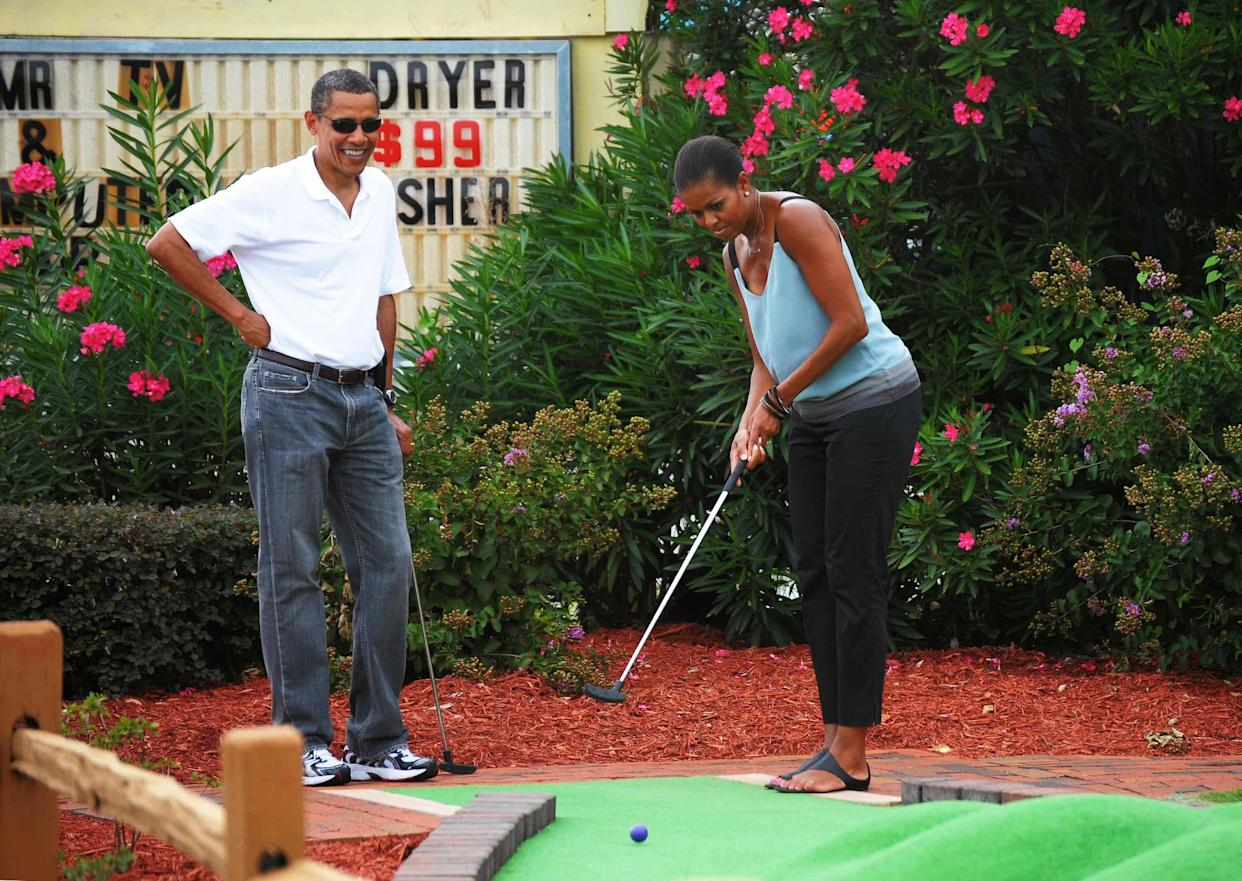 Barack Obama watches as Michelle Obama putts during a round of mini golf at Pirate's Island Golf on Aug. 14, 2010, in Panama City Beach, Florida.