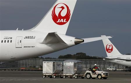 A airport worker drives a luggage transport vehicle past one of the company's Boeing Co's 787 Dreamliner plane and a Beoing 767 at Narita international airport in Narita