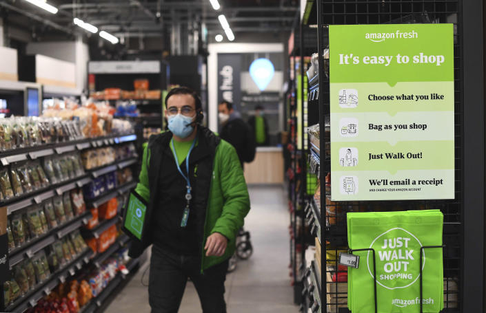 The Amazon Fresh grocery store opens in London, Thursday March 4, 2021, where a sign explains for shoppers to pick up items and walk out of the store, contactless, without the need for a till. Customers will scan a QR code on their way into the store, with cameras and technology identifying the items that shoppers take from the shelves and their account automatically paid. (Victoria Jones/PA via AP)