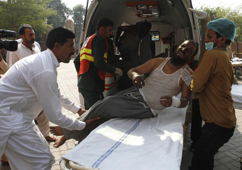 Hospital staff shift a man who was injured in a train fire, to a hospital in Multan, Pakistan, Thursday, Oct. 31, 2019. A massive fire engulfed three carriages of the train traveling in the country's eastern Punjab province (AP Photo/Asim Tanveer)