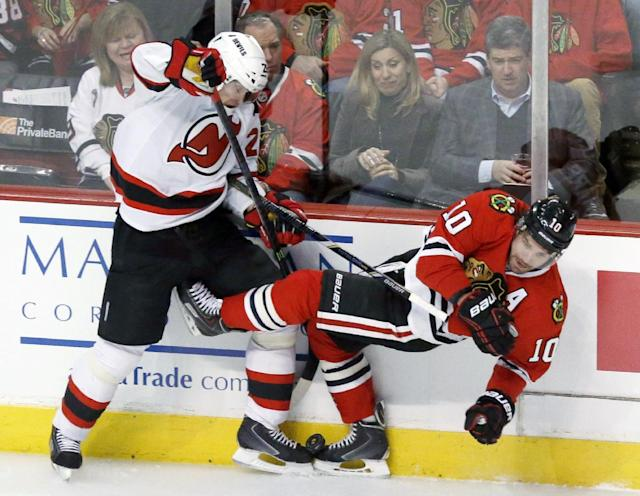 New Jersey Devils defenseman Anton Volchenkov, left, checks Chicago Blackhawks left wing Patrick Sharp (10) along the boards during the first period of an NHL hockey game Monday, Dec. 23, 2013, in Chicago. (AP Photo/Charles Rex Arbogast)