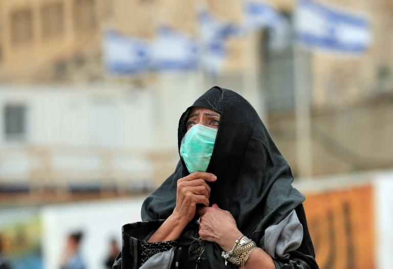 A woman at Jerusalem's nearly deserted Western Wall, Judaism's holiest site, after Israel has imposed some of the world's tightest restrictions to contain the new coronavirus