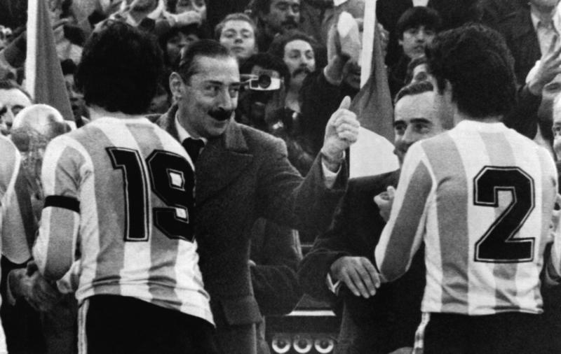 "FILE - In this June 25, 1978 file photo, Argentina's President Jorge Rafael Videla, center, gives a thumbs up to Osvaldo Ardiles, right, and captain Daniel Passarella, left, holding the World Cup, following the World Cup Final between Argentina and Netherlands in Buenos Aires, Argentina. Argentina defeated Netherlands 3-1 after extra time. The former Argentine dictator died of natural causes Friday, May 17, 2013, while serving life sentences at the Marcos Paz prison for crimes against humanity. Videla took power in a 1976 coup and led a military junta that killed thousands of his fellow citizens in a dirty war to eliminate ""subversives."" He was 87. (AP Photo/ File)"