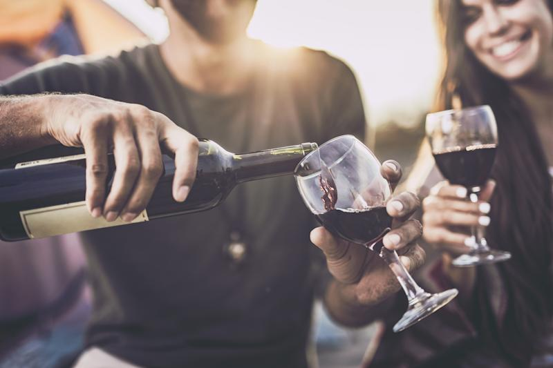 Close up of a couple drinking wine outdoors while man is pouring it into a glass.